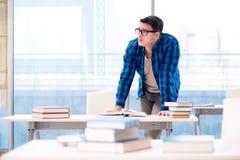Estudiante que estudia en la biblioteca vacía con el libro que se prepara para ex Fotografía de archivo libre de regalías