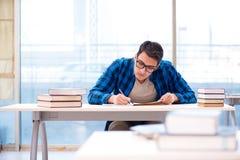 Estudiante que estudia en la biblioteca vacía con el libro que se prepara para ex Foto de archivo