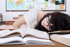 Estudiante que estudia en la clase y el sueño en los libros Imagen de archivo libre de regalías