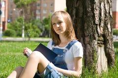 Estudiante que estudia en la hierba Foto de archivo libre de regalías