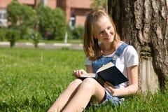 Estudiante que estudia en la hierba Fotos de archivo libres de regalías