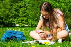 Estudiante que estudia en parque con smartphone Sentada y lectura felices alegres de la estudiante del adolescente afuera en camp Imagen de archivo libre de regalías
