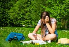 Estudiante que estudia en parque con smartphone Sentada y lectura felices alegres de la estudiante del adolescente afuera en camp Foto de archivo
