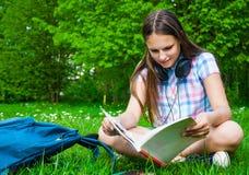 Estudiante que estudia en parque Sentada y lectura felices alegres de la estudiante del adolescente afuera en campus universitari Imágenes de archivo libres de regalías