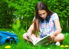 Estudiante que estudia en parque Sentada y lectura felices alegres de la estudiante del adolescente afuera en campus universitari Fotos de archivo libres de regalías