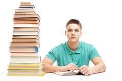 Estudiante que estudia en una tabla con la alta pila de libros Foto de archivo