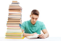 Estudiante que estudia en una tabla con una pila de libros Imágenes de archivo libres de regalías