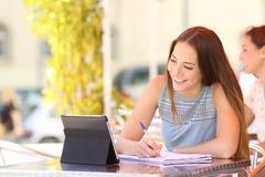 Estudiante que estudia tomando notas con una tableta Fotografía de archivo libre de regalías