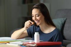 Estudiante que estudia tomando una píldora de la vitamina Imágenes de archivo libres de regalías