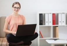 Estudiante que estudia usando un ordenador portátil que se sienta en la posición de loto Fotos de archivo libres de regalías