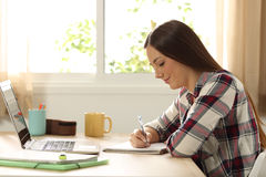 Estudiante que estudia y que toma notas en casa Imagen de archivo