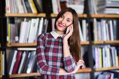 Estudiante que habla en el teléfono en la biblioteca chica joven que habla en el teléfono en la biblioteca Imagen de archivo