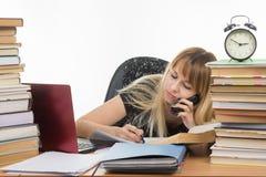 Estudiante que habla en la escritura del teléfono algo en un trozo de papel Fotos de archivo