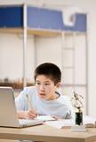 Estudiante que hace la preparación y que usa la computadora portátil Fotografía de archivo libre de regalías