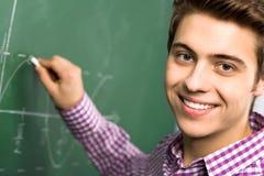 Estudiante que hace matemáticas en la pizarra Fotos de archivo libres de regalías