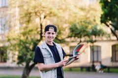 Estudiante que lee un cuaderno en el fondo de la universidad Un adolescente en el fondo de un campus de la universidad Imagen de archivo libre de regalías
