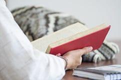Estudiante que lee un libro en biblioteca Imágenes de archivo libres de regalías