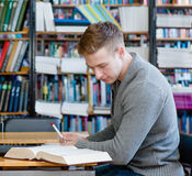 Estudiante que lee un libro en la biblioteca Fotos de archivo