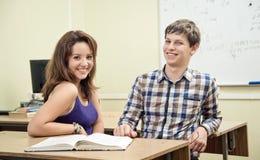 Estudiante que lee un libro en la sala de clase Fotos de archivo