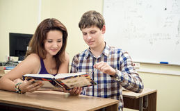 Estudiante que lee un libro en la sala de clase Foto de archivo