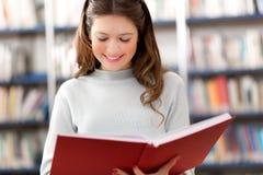 Estudiante que lee un libro en una biblioteca Fotos de archivo