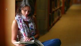 Estudiante que lee un libro que se sienta por una ventana almacen de metraje de vídeo