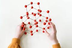 Estudiante que lleva a cabo el modelo de estructura molecular Clase de la ciencia Opinión de perspectiva personal foto de archivo