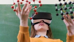 Estudiante que lleva los vidrios de la realidad virtual, llevando a cabo el modelo de estructura molecular Clase de la ciencia, e imagenes de archivo