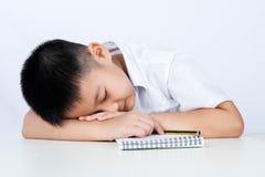 Estudiante que lleva Uniform Sleeping de Little Boy del chino asiático en el DES Imagenes de archivo