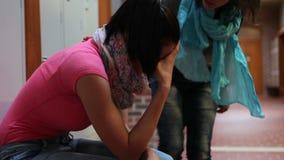 Estudiante que llora en el vestíbulo que es confortado por el amigo almacen de video