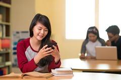 Estudiante que manda un SMS Imagen de archivo