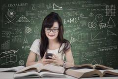 Estudiante que manda un SMS en la clase Imágenes de archivo libres de regalías
