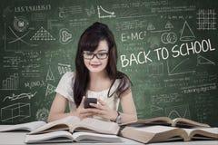 Estudiante que manda un SMS en la sala de clase Fotografía de archivo libre de regalías