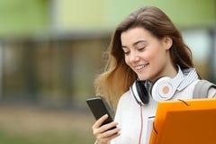Estudiante que manda un SMS en un teléfono cerca de la universidad Imagen de archivo