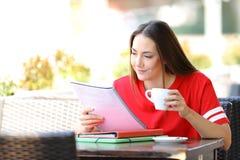 Estudiante que memoriza las notas que sostienen una taza de caf? en una barra imagen de archivo libre de regalías