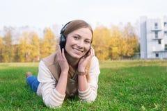 Estudiante que miente en hierba verde y que escucha los auriculares Foto de archivo