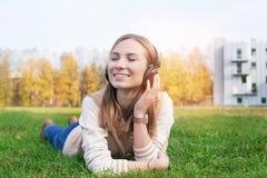 Estudiante que miente en hierba y música que escucha en los auriculares Foto de archivo libre de regalías