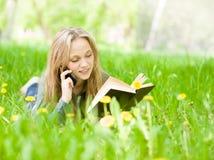 Estudiante que miente en la hierba que lee un libro y que habla en la hierba verde Imagen de archivo