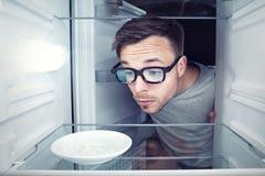 Estudiante que mira dentro de un refrigerador vacío Foto de archivo libre de regalías