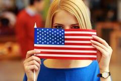 Estudiante que mira a escondidas detrás de la bandera de los E.E.U.U. Fotografía de archivo libre de regalías