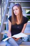 Estudiante que piensa con el cuaderno y el lápiz Fotos de archivo