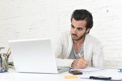 Estudiante que prepara proyecto de la universidad u hombre de negocios del freelancer del estilo del inconformista que trabaja co foto de archivo