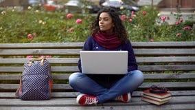 Estudiante que reflexiona sobre proyecto mientras que trabaja en el ordenador portátil, sentándose en el banco al aire libre Imagen de archivo