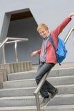 Estudiante que resbala abajo de la verja en la escalera Imagenes de archivo