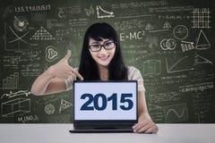 Estudiante que señala los números 2015 en el ordenador portátil Fotos de archivo libres de regalías