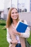 Estudiante que se coloca con el libro en sus manos y risa Fotografía de archivo libre de regalías