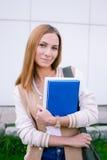 Estudiante que se coloca con el libro y que mira la cámara Imagen de archivo libre de regalías