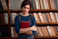 Estudiante que se coloca con los ojos cerrados en biblioteca Imagen de archivo
