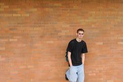 Estudiante que se coloca delante de la pared de ladrillo Fotografía de archivo