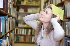 Estudiante que se coloca en el estante en biblioteca vieja Fotos de archivo